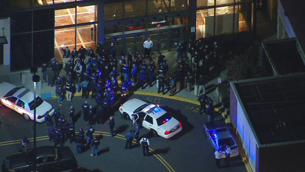 Description of . In this image provided by News 12 New Jersey, authorities converge on the Garden State Plaza Mall, late Monday, Nov. 4, 2013, in Paramus, N.J., after there were reports of multiple shots being fired inside the mall. (AP Photo/News 12 New Jersey)