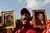 A supporter of Venezuela's late President Hugo Chavez holds images of him while the coffin containing his body passes in the street, from the hospital where he died on Tuesday to a military academy where it will remain until his funeral in Caracas, Venezuela, Wednesday, March 6, 2013.  (AP Photo/Rodrigo Abd)