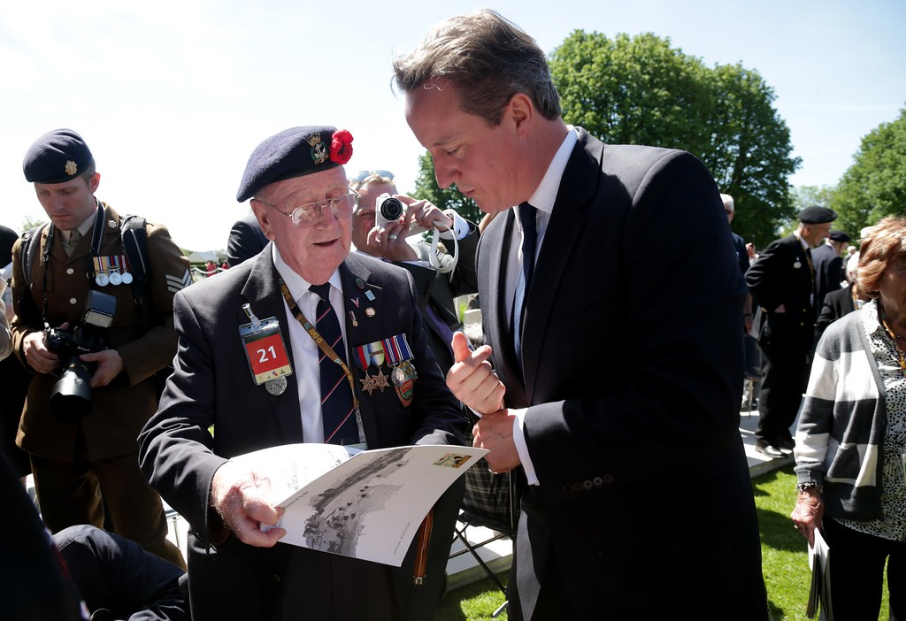 Description of . Prime Minister David Cameron stops to chat with veterans at Bayeux Cemetery during D-Day 70th anniversary commemorations on June 6, 2014 in Bayeux, France.  (Photo by Matt Cardy/Getty Images)
