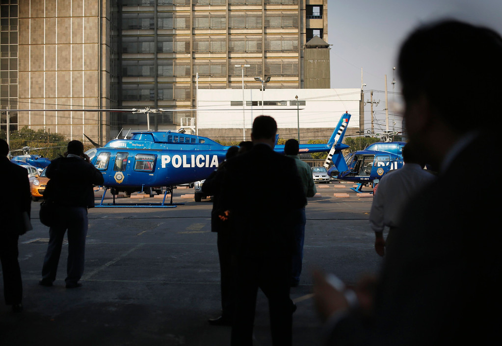 Description of . Police helicopters are stationed in the parking lot of state oil giant Pemex in Mexico City January 31, 2013. A powerful explosion rocked the Pemex building on Thursday, killing at least 14 people and injuring 100 others. The blast hit the lower floors of the downtown tower block, throwing debris into the streets and sending workers running outside.  REUTERS/Tomas Bravo
