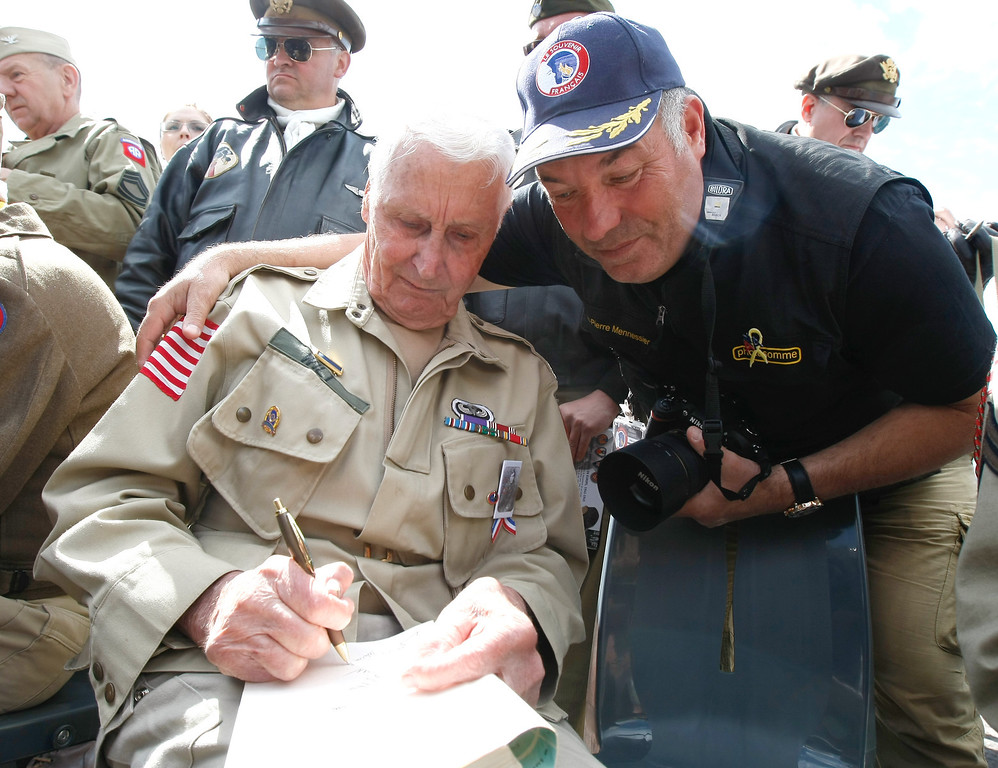 Description of . U.S WWII veteran Warren Wilt, 91-years-old  from Abbyville, Kansas, left,  who landed on Picauville France on June 6, 1944, with the 82nd Airborne Division signs a book, for Jean-Pierre Mennessier, after a ceremony at the Memorial of Airborne and US Air Force, in Picauville, France, as part of the commemoration of the 70th D-Day anniversary, Thursday, June 5, 2014. (AP Photo/Claude Paris)