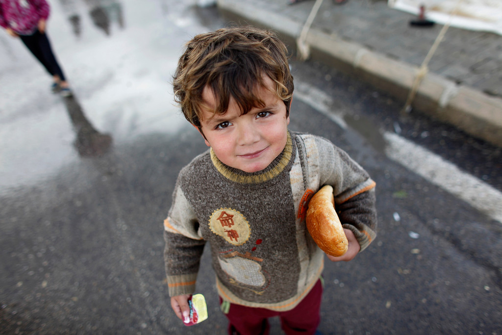 Description of . A Syrian refugee boy holds bread at the Boynuyogun refugee camp on the Turkish-Syrian border in Hatay province February 8, 2012.REUTERS/Murad Sezer