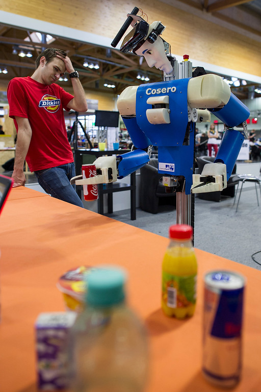 Description of . MAGDEBURG, GERMANY - APRIL 26:  Participants check a service robot at the 2013 RoboCup German Open tournament on April 26, 2013 in Magdeburg, Germany. The three-day tournament is hosting 43 international teams and 158 German junior teams that compete in a variety of disciplines, including soccer, rescue and dance.  (Photo by Jens Schlueter/Getty Images)