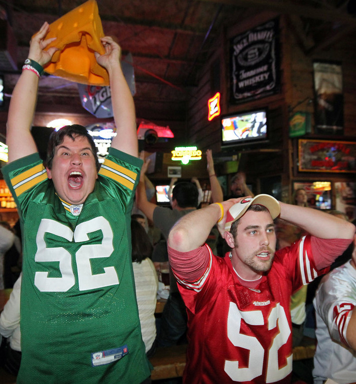 Description of . Greenbay Packers fan Casey Lansdon, left, and San Francisco 49ers fan Ryan Dunn react to a Packers touchdown as they watch a broadcast of an NFC divisional playoff NFL football game on Saturday, Jan. 12, 2013, at The Graduate in Chico, Calif.  (AP Photo/The Chico Enterprise-Record, Jason Halley)