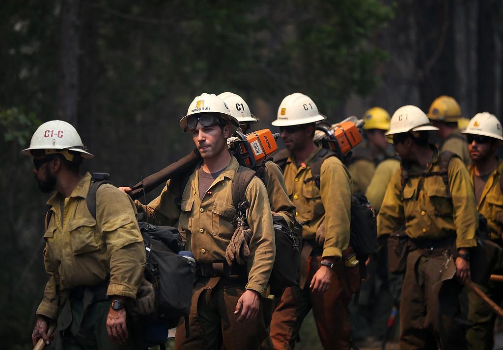 Description of . GROVELAND, CA - AUGUST 22:  U.S. Forest Service firefighters move into position while battling the Rim Fire on August 22, 2013 in Groveland, California. The Rim Fire continues to burn out of control and threatens 2,500 homes outside of Yosemite National Park. Over 1,000 firefighters are battling the blaze that was reduced to only 2 percent containment after it nearly tripled in size overnight.  (Photo by Justin Sullivan/Getty Images)