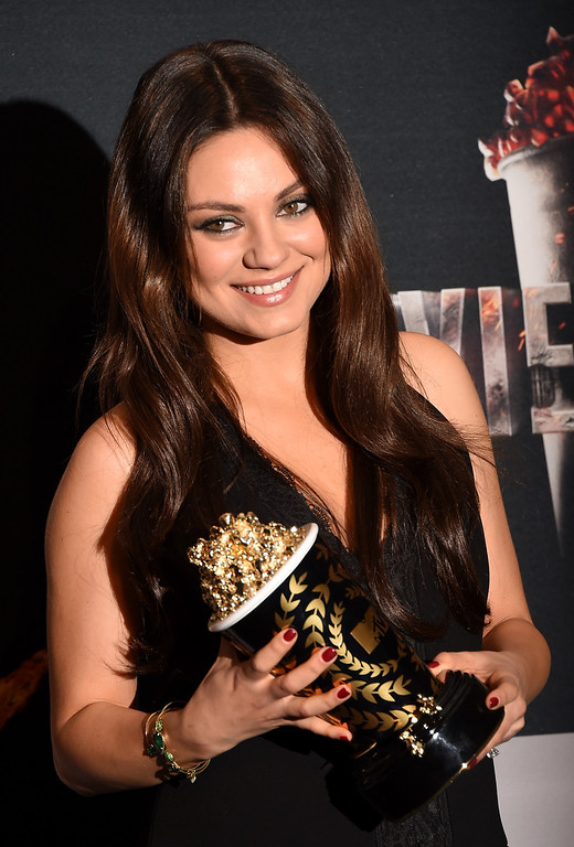 Description of . Actress Mila Kunis poses with the Best Villain award for 'Oz The Great and Powerful' in the press room during the 2014 MTV Movie Awards at Nokia Theatre L.A. Live on April 13, 2014 in Los Angeles, California.  (Photo by Jason Merritt/Getty Images for MTV)