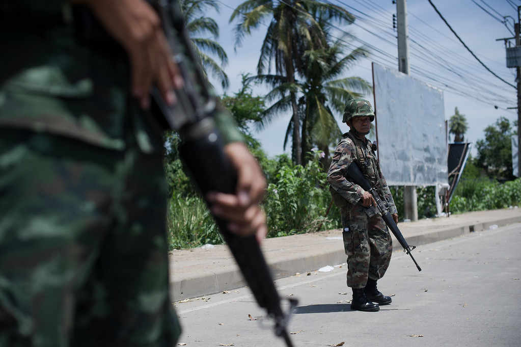 Description of . Thai army soldiers stand at a checkpoint near where pro-government ''Red shirts'' have been rallying for days on the outskirts of Bangkok on May 20, 2014. AFP PHOTO/ Nicolas ASFOURI/AFP/Getty Images