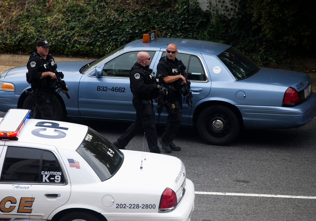 Description of . Capitol Hill police officers respond to a shooting on Capitol Hill in Washington, Thursday, Oct. 3, 2013. Police say the U.S. Capitol has been put on a security lockdown amid reports of possible shots fired outside the building.  (AP Photo/ Evan Vucci)