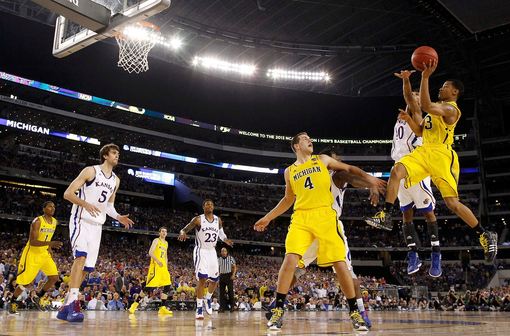 Description of . Michigan Wolverines guard Trey Burke shoots against the Kansas Jayhawks during overtime in their South Regional NCAA men\'s basketball game in Arlington, Texas March 29, 2013. REUTERS/Jim Young