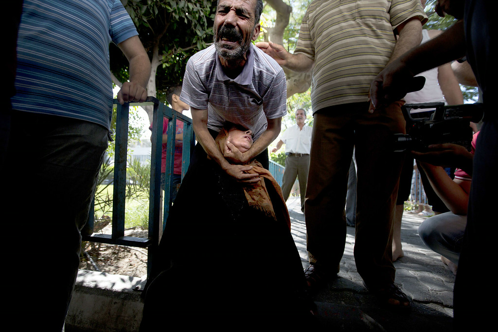 Description of . Palestinian relatives of the four boys killed in Israeli bombardment, all from the Bakr family, cry at the morgue of the hospital in Gaza City, on July 16, 2014. Four children were killed and several injured at a beach in Gaza City medics said, in Israeli shelling witnessed by AFP journalists. The strikes appeared to be the result of shelling by the Israeli navy against an area with small shacks used by fishermen. The deaths raised the overall toll in nine days of violence in Gaza to 213. AFP PHOTO / MAHMUD HAMS/AFP/Getty Images