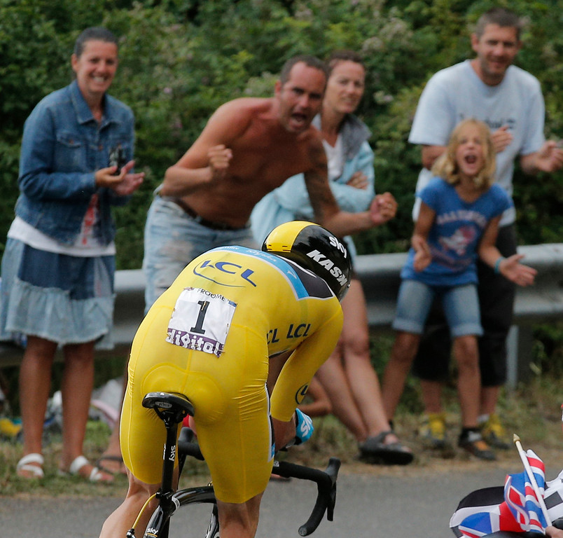 Description of . Spectators cheers as stage winner Christopher Froome of Britain, wearing the overall leader's yellow jersey, passes during the seventeenth stage of the Tour de France cycling race an individual time trial over 32 kilometers (20 miles) with start in Embrun and finish in Chorges, France, Wednesday July 17, 2013. (AP Photo/Christophe Ena)
