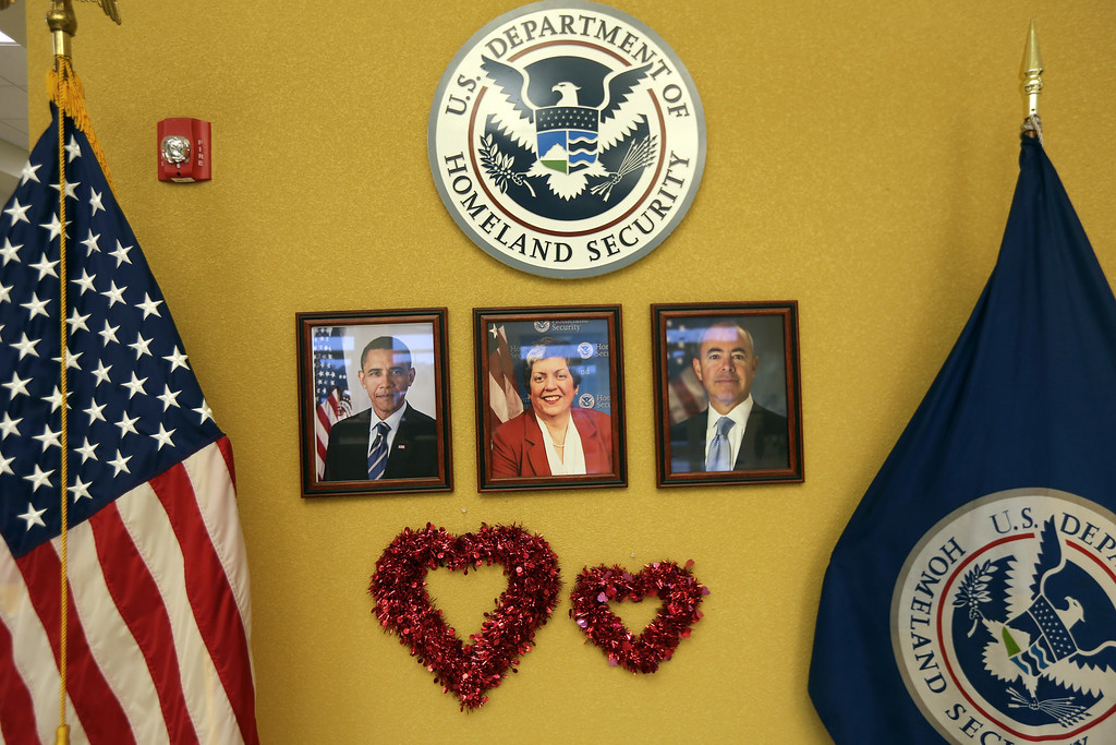 Description of . Portraits of U.S. President Barack Obama, U.S. Homeland Security Secretary Janet Napolitano and Alejandro Mayorkas, Director of U.S. Citizenship and Immigration Services, (USCIS), are adorned with hearts at a special Valentine's Day naturalization ceremony for married couples on February 14, 2013 in Tampa, Florida. The U.S. Citizenship and Immigration Service (USCIS) held the Valentine's Day ceremony in Tampa for 28 married couples from 15 different countries.  (Photo by John Moore/Getty Images)