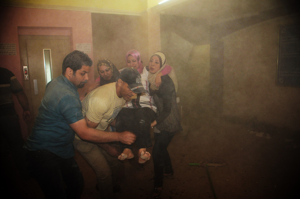 . Ministry of Health staff carry a wounded colleague during a car bomb attack at the Health Department in Baghdad, Iraq, Monday, June 4, 2012. A suicide bomber detonated explosives in a car outside Iraq\'s main religious affairs office for Shiite Muslims, tearing down part of the three-story building and killed and wounded scores of people, police said. (AP Photo/Adil al-Khazali)