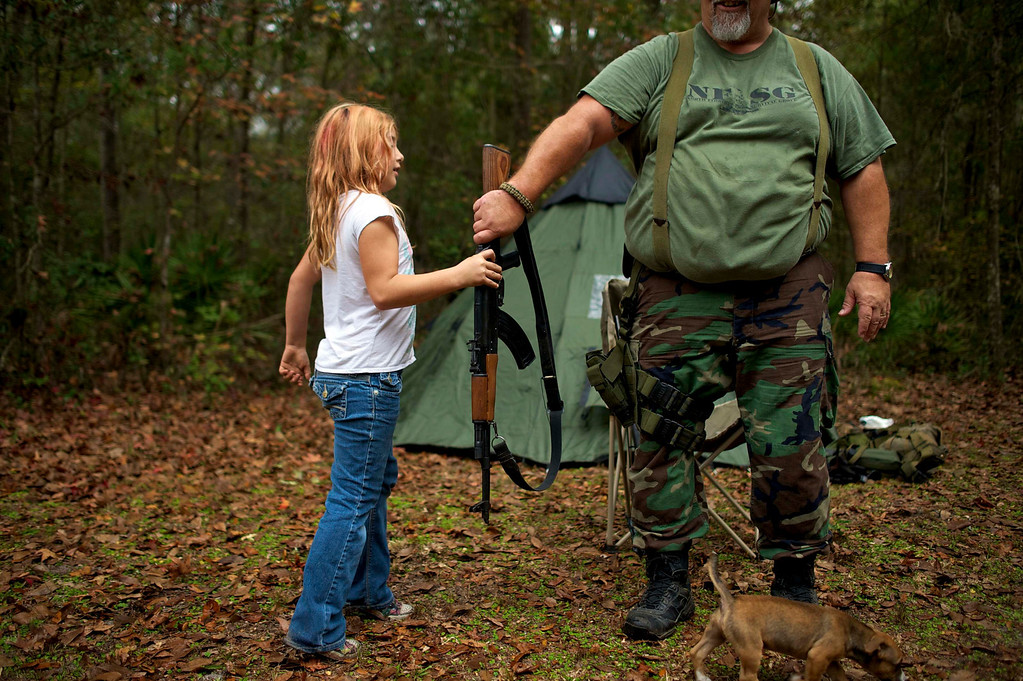 ". Brianna, 9, of the North Florida Survival Group hands an AK-47 rifle to Jim Foster, 57, the group\'s leader, before heading out to conduct enemy contact drills during a field training exercise in Old Town, Florida, December 8, 2012. The group trains children and adults alike to handle weapons and survive in the wild. The group passionately supports the right of U.S. citizens to bear arms and its website states that it aims to teach ""patriots to survive in order to protect and defend our Constitution against all enemy threats\"". Picture taken December 8, 2013.   REUTERS/Brian Blanco"