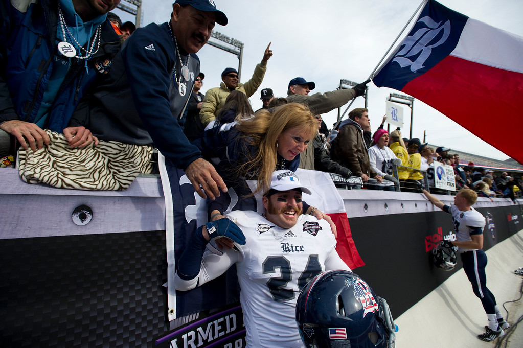 Description of . Paul Porras #24 of the Rice Owls poses for a photo with fans after defeating  the Air Force Falcons on December 29, 2012 in the Bell Helicopter Armed Forces Bowl at Amon G. Carter Stadium in Fort Worth, Texas.  (Photo by Cooper Neill/Getty Images)