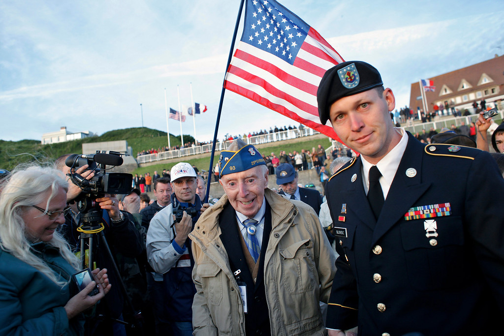 Description of . World War II veteran of the U.S. army 29th Infantry Division, Don McCarthy, 90, from Rhode Island, center, arrives for a D-Day commemoration, on Omaha Beach, western France, Friday June 6, 2014. Veterans and Normandy residents are paying tribute to the thousands who gave their lives in the D-Day invasion of Nazi-occupied France 70 years ago.  (AP Photo/Thibault Camus)