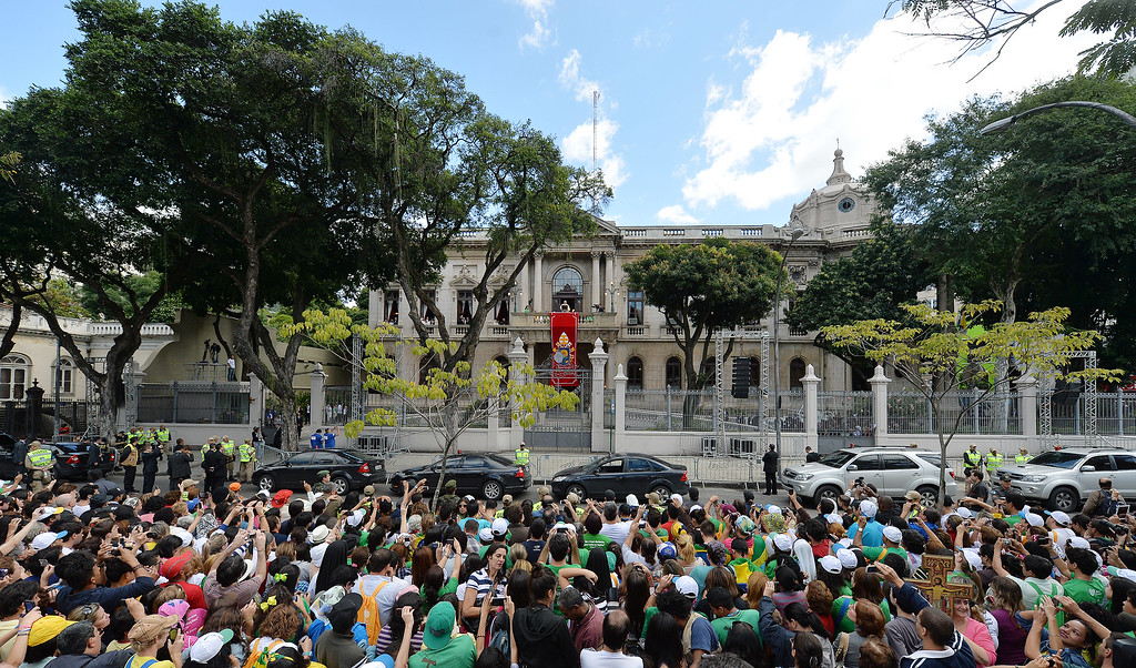 Description of . People gather to listen to Pope Francis, top center above red banner, give Angelus noon prayer from Sao Joaquim Palace in Rio de Janeiro, Brazil, Friday, July 26, 2013. Pope Francis is on the fifth day of his trip to Brazil where he will attend the 2013 World Youth Day in Rio. (AP Photo/Luca Zennaro, Pool)