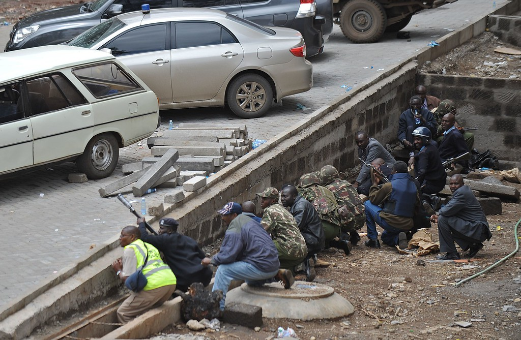 Description of . Kenyan security personnel, crouched behind a ledge, watch on September 23, 2013 a column of smoke rise from the besieged Westgate shopping mall in Nairobi following a loud explosion.          AFP PHOTO / TONY  KARUMBA/AFP/Getty Images