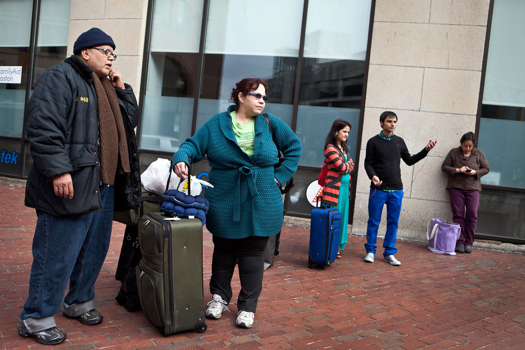 Description of . (L-R) Stranded travelers Angel Valentin and Rosa Valentin of North Dakota and Puna Nepal and Tika Lamichaney of New York stand outside South Station on April 19, 2013 in Boston, Massachusetts. South Station was shut down and heavily guarded with police in response to the early morning shootings in Cambridge and Watertown, Massachusetts. (Photo by Kayana Szymczak/Getty Images)