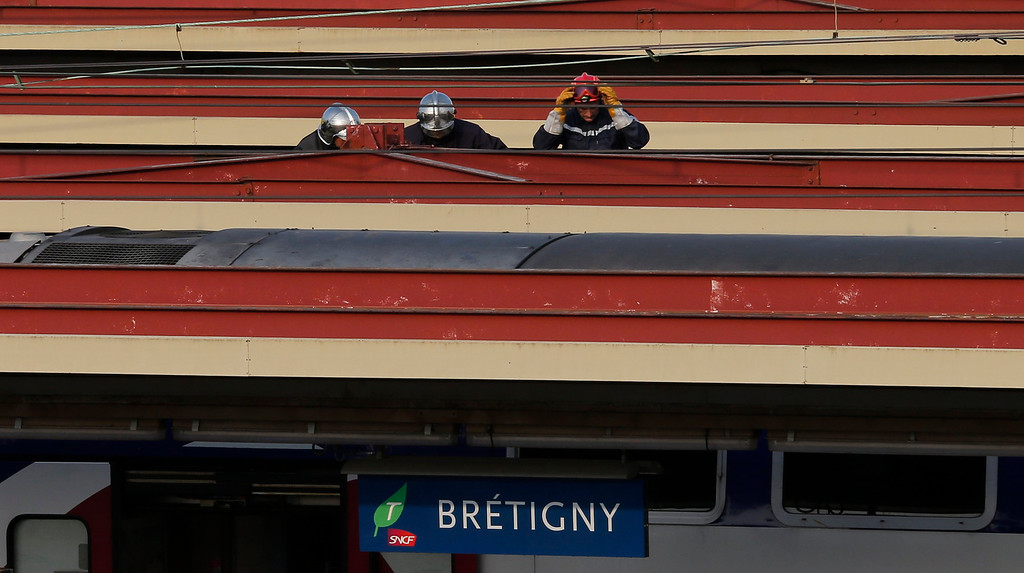Description of . Firefighters are seen on the roof of train after an intercity train accident at the Bretigny-sur-Orge station near Paris July 12, 2013.  REUTERS/Benoit Tessier