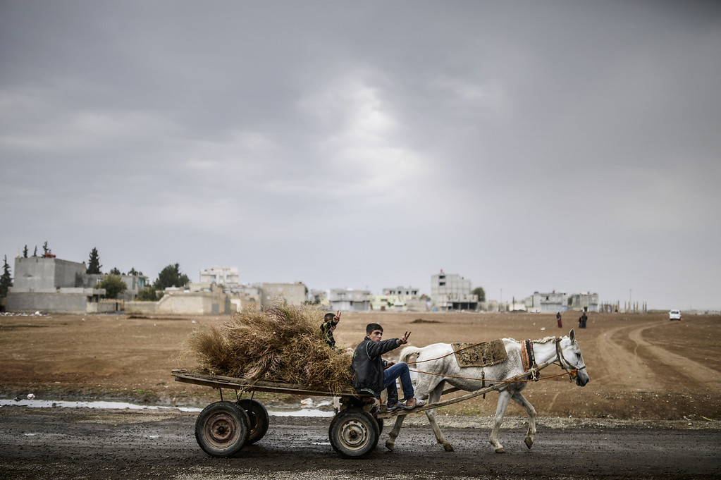 Description of . Kurdish boys ride a horse cart during a rainy day in Suruc, a rural district of Sanliurfa Province, on October 30, 2014. Heavily armed Kurdish peshmerga fighters were on their way by land and by air, joining militias defending the Syrian border town of Kobane, also known as Ain al-Arab, from the Islamic State group after setting off from Iraq. Kobane's Kurdish defenders have been eagerly waiting for the peshmerga since Turkey last week said it would allow them to traverse its territory to enter the town. BULENT KILIC/AFP/Getty Images