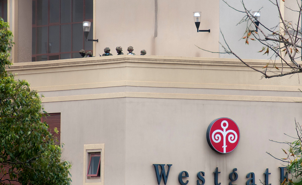 Description of . Kenyan soldiers are seen on an upper floor balcony of the Westgate Mall following large explosions and heavy gunfire, in Nairobi, Kenya Monday, Sept. 23, 2013. F. (AP Photo/Jonathan Kalan)