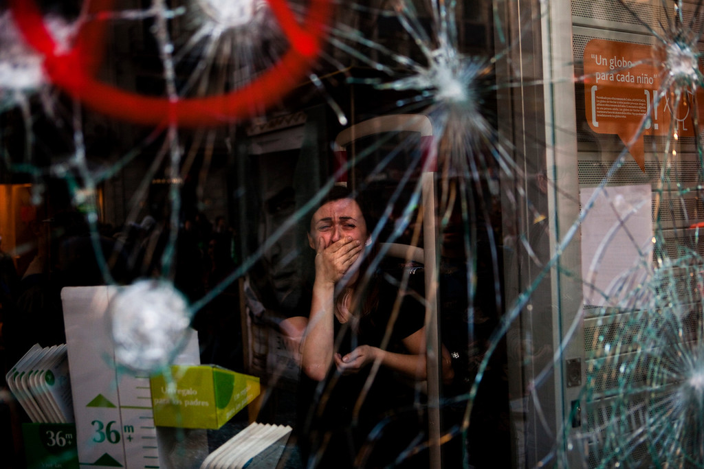 Description of . In this March 29, 2012 file photo, Mireia Arnau, 39, reacts behind the broken glass of her shop stormed by demonstrators during clashes at the general strike in Barcelona. Spanish workers livid over labor reforms they see as flagrantly pro-business staged a nationwide strike and tried to bring the country to a halt by blocking traffic, closing factories and clashing with police in rowdy demonstrations. (AP Photo/Emilio Morenatti, File)