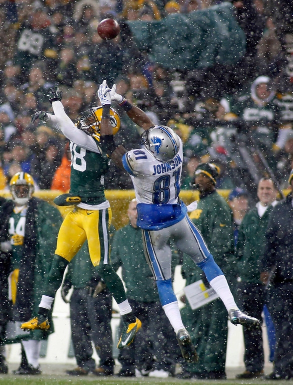 Description of . Green Bay Packers cornerback Tramon Williams (L) and Detroit Lions wide receiver Calvin Johnson go up for a pass during the first half of a NFL football game in Green Bay, Wisconsin December 9, 2012. REUTERS/Darren Hauck