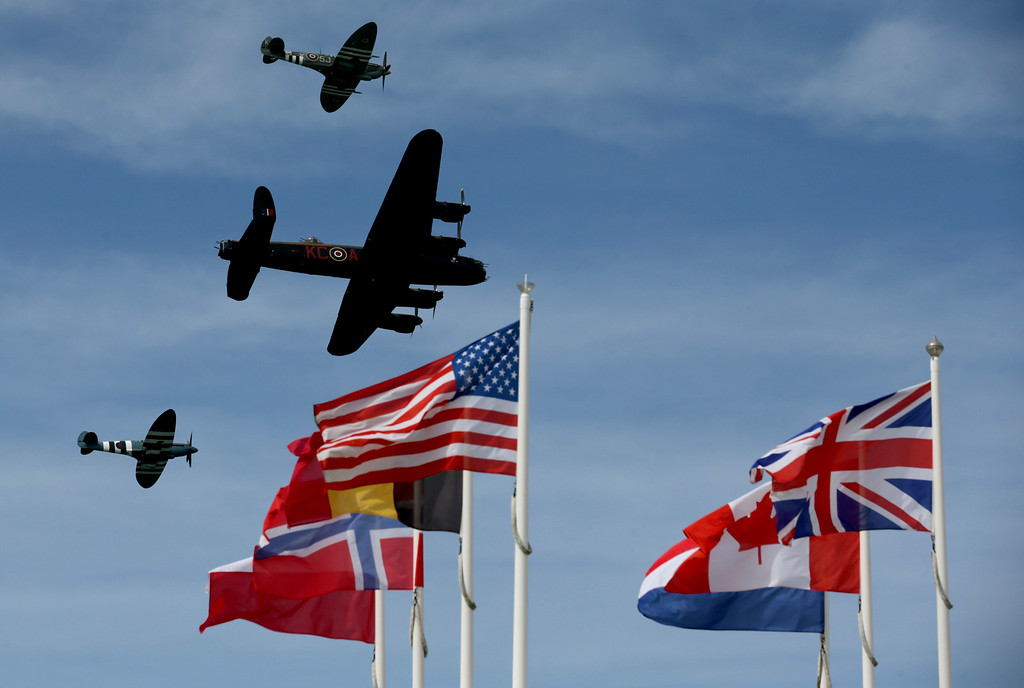 Description of . The Battle of Britain Memorrial flight passes flags at Arrowmanches-Les-Bains during D-Day 70 Commemorations on June 6, 2014 near Bayeux, France.  (Photo by Matt Cardy/Getty Images)