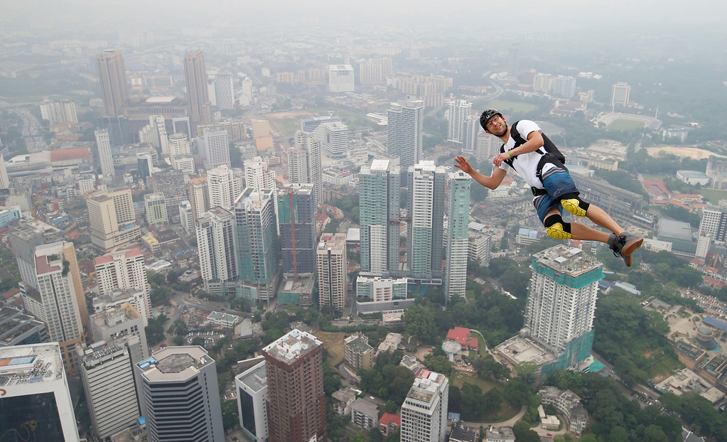 Description of . Base jumper Kristian Moxnes of Norway leaps from the 300-meter Open Deck of the Malaysia's landmark Kuala Lumpur Tower during the International Tower Jump in Kuala Lumpur, Friday, Sept. 27, 2013.  (AP Photo/Vincent Thian)