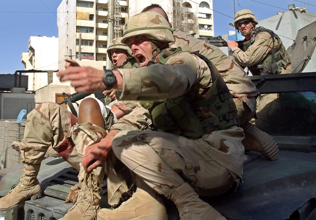 Description of . U.S. Army soldiers rush to evacuate an injured comrade in the center of Baghdad, Iraq, after thunderous explosions at the capital, Tuesday, May 25, 2004. A U.S. helicopter landed in the square and evacuated at least one wounded person as American troops and military vehicles provided security. (AP Photo/Muhammed Muheisen)
