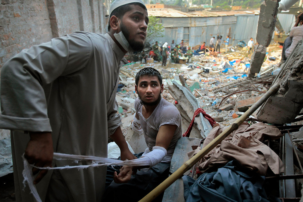 Description of . A Bangladeshi rescuer dresses the wound of another who got injured during a rescue operation at the site of a building that collapsed Wednesday in Savar, near Dhaka, Bangladesh, Thursday, April 25, 2013. (AP Photo/A.M.Ahad)