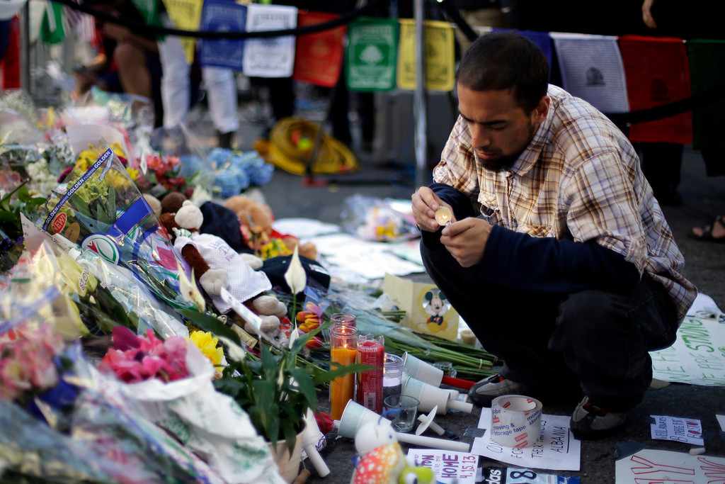 Description of . Richard Maldonado lights a candle at a makeshift memorial on Boylston Street near the finish line of Monday's Boston Marathon explosions, which killed at least three and injured more than 140,  Wednesday, April 17, 2013, in Boston. (AP Photo/Matt Rourke)