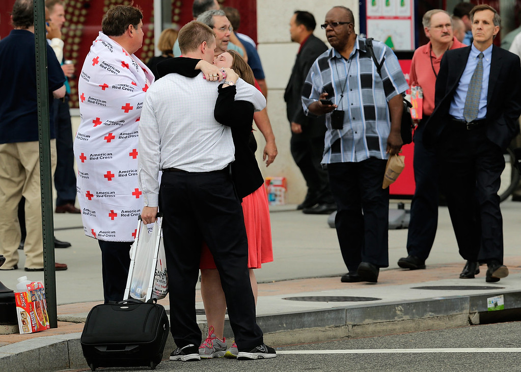 . A man and woman embrace while reuniting at a gathering point for family members of Navy Yard employees that was set up inside Nationals Park in the wake of the shooting September 16, 2013 in Washington, DC. Police believe at least one gunman shot and killed at least 12 people and wounded others in an incident that put parts of the city on lockdown. (Photo by Win McNamee/Getty Images)