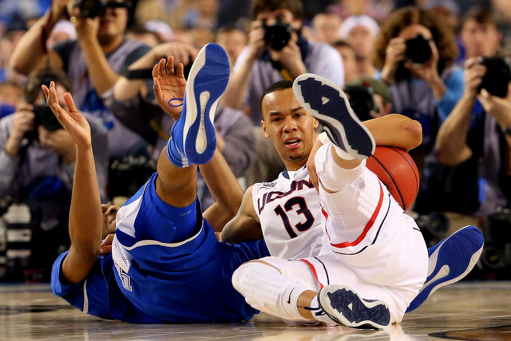 Description of . ARLINGTON, TX - APRIL 07:  Shabazz Napier #13 of the Connecticut Huskies falls to the ground as Marcus Lee #00 of the Kentucky Wildcats defends during the NCAA Men\'s Final Four Championship at AT&T Stadium on April 7, 2014 in Arlington, Texas.  (Photo by Ronald Martinez/Getty Images)