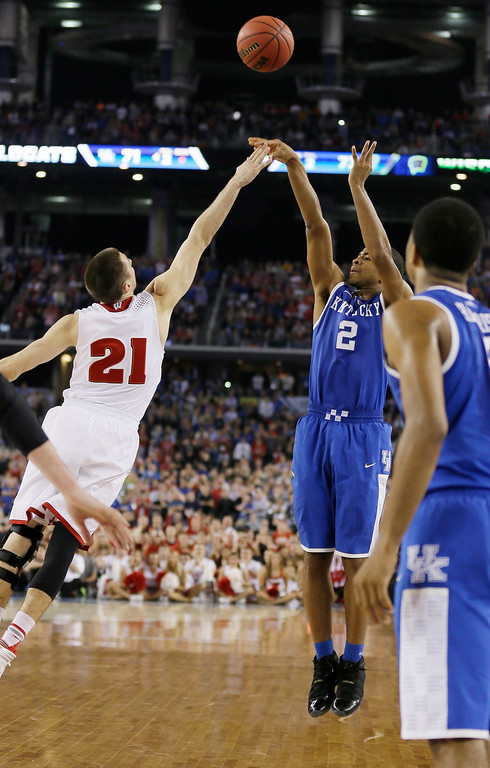 Description of . Kentucky guard Aaron Harrison (2) makes a three-point basket in the final seconds over Wisconsin guard Josh Gasser (21) to win the game 74-73 during their NCAA Final Four tournament college basketball semifinal game Saturday, April 5, 2014, in Arlington, Texas. (AP Photo/Charlie Neibergall)