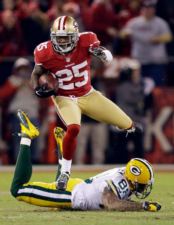 Description of . San Francisco 49ers cornerback Tarell Brown (25) returns an interception from Green Bay Packers quarterback Aaron Rodgers as he leaps over Green Bay Packers tight end Jermichael Finley (88) in the first half of an NFC divisional playoff NFL football game in San Francisco, Saturday, Jan. 12, 2013. (AP Photo/Marcio Jose Sanchez)