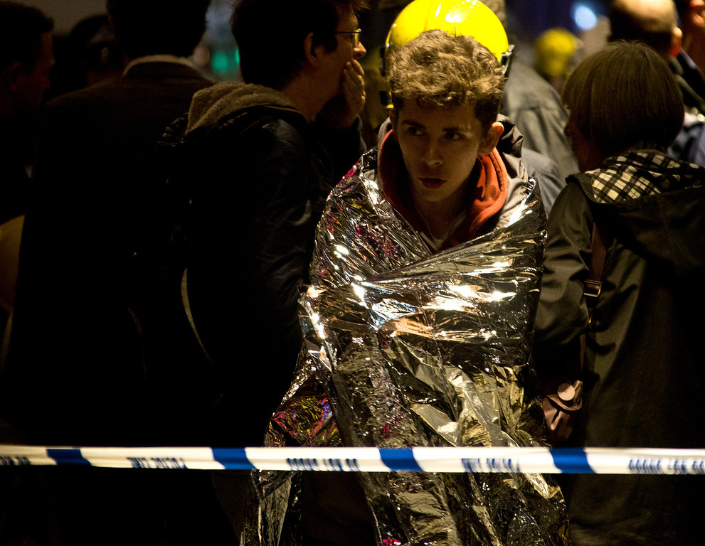 """. A man wraps himself in an emergency foil blanket provided by rescue services following an incident at the Apollo Theatre, in London\'s Shaftesbury Avenue, Thursday evening, Dec. 19, 2013 during a performance , with police saying there were \""""a number\"""" of casualties. (AP Photo by Joel Ryan, Invision)"""