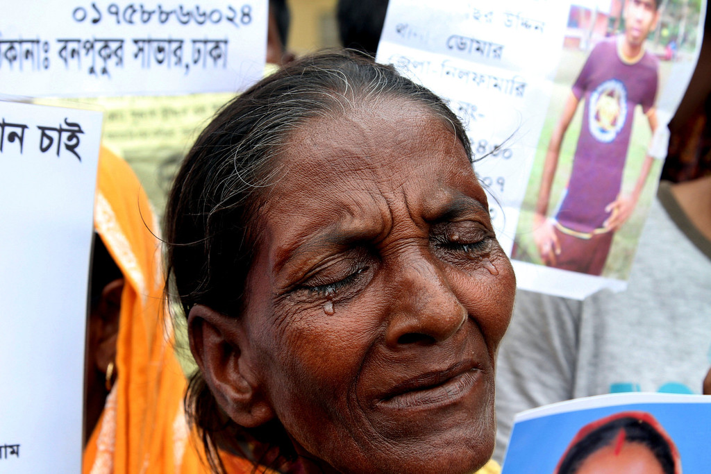 Description of . A Bangladeshi woman weeps as Bangladeshi people hold photographs of their relatives whom they believe are trapped in the rubbles of a building that collapsed in Savar, outskirts of Dhaka, Bangladesh, Tuesday, April 30, 2013.  (AP Photo/Palash Khan)