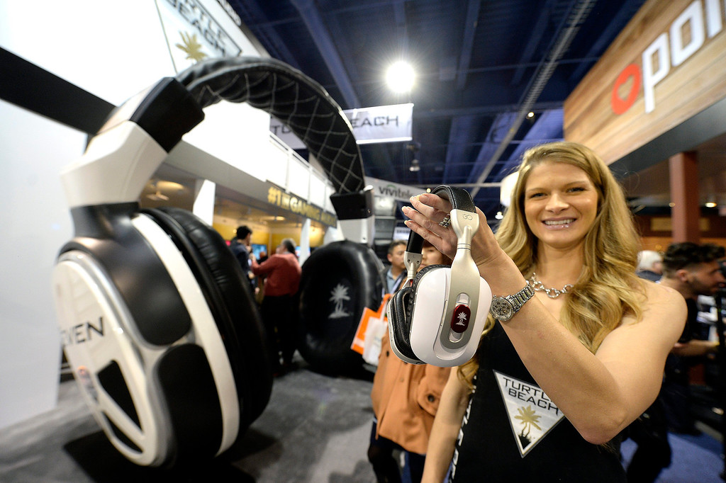 Description of . A hostess holds up Turtle Beach wireless headphones at the Las Vegas Convention Center for the 2014 International CES (Consumer Electronics Show) in Las Vegas, Nevada, USA, 08 January 2014. CES, the world's largest annual consumer technology trade show, runs from 7-10 January and is expected to feature 3,200 exhibitors displaying their latest products and services to about 150,000 attendees.  EPA/MICHAEL NELSON