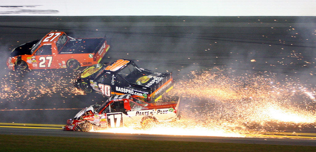 Description of . Timothy Peters (17) collides Ryan Truex (30) as Jeff Agnew (27) gets by during the NASCAR Truck Series auto race Friday, Feb. 22, 2013, at Daytona International Speedway in Daytona Beach, Fla. (AP Photo/Ron Sanders)