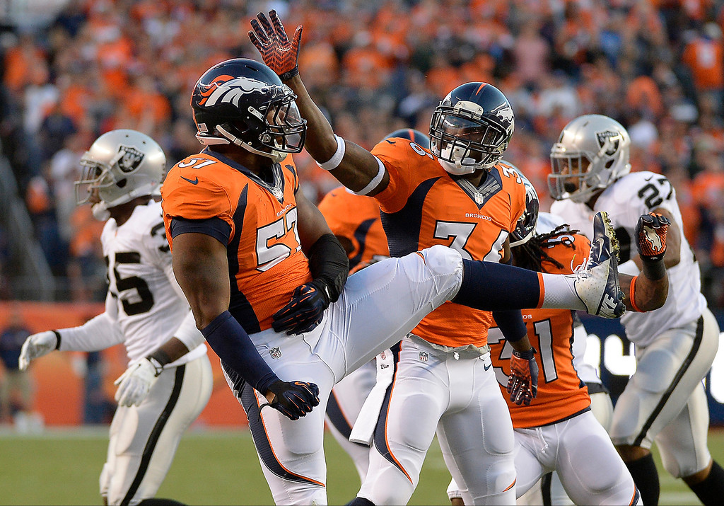 Description of . Denver Broncos linebacker Adrian Robinson (57) and Denver Broncos cornerback Kayvon Webster (36) celebrate after a play in the first quarter. The Denver Broncos took on the Oakland Raiders at Sports Authority Field at Mile High in Denver on September 23, 2013. (Photo by John Leyba/The Denver Post)