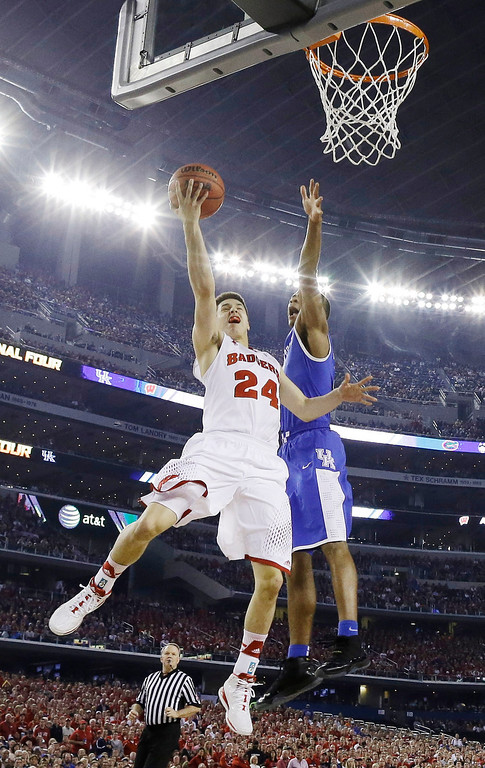 Description of . Wisconsin guard Bronson Koenig (24) shoots against Kentucky guard Aaron Harrison during the first half of the NCAA Final Four tournament college basketball semifinal game Saturday, April 5, 2014, in Arlington, Texas. (AP Photo/David J. Phillip)