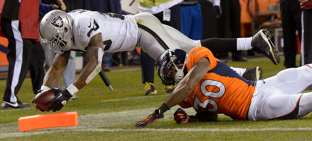 Description of . Oakland Raiders running back Darren McFadden (20) dives for the goal line as Denver Broncos strong safety David Bruton (30) attempts to drive hime out of bounds. The Denver Broncos took on the Oakland Raiders at Sports Authority Field at Mile High in Denver on September 23, 2013. (Photo by Joe Amon/The Denver Post)