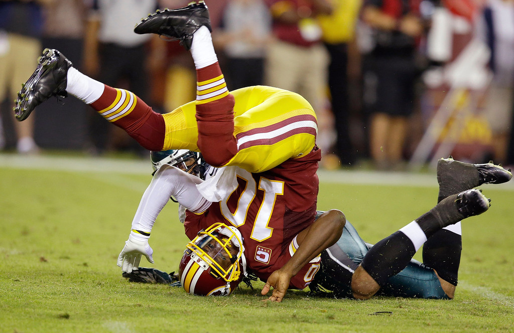 Description of . Washington Redskins quarterback Robert Griffin III rolls onto his head after he is tackled by Philadelphia Eagles outside linebacker Mychal Kendricks during the first half of an NFL football game in Landover, Md., Monday, Sept. 9, 2013. (AP Photo/Alex Brandon)