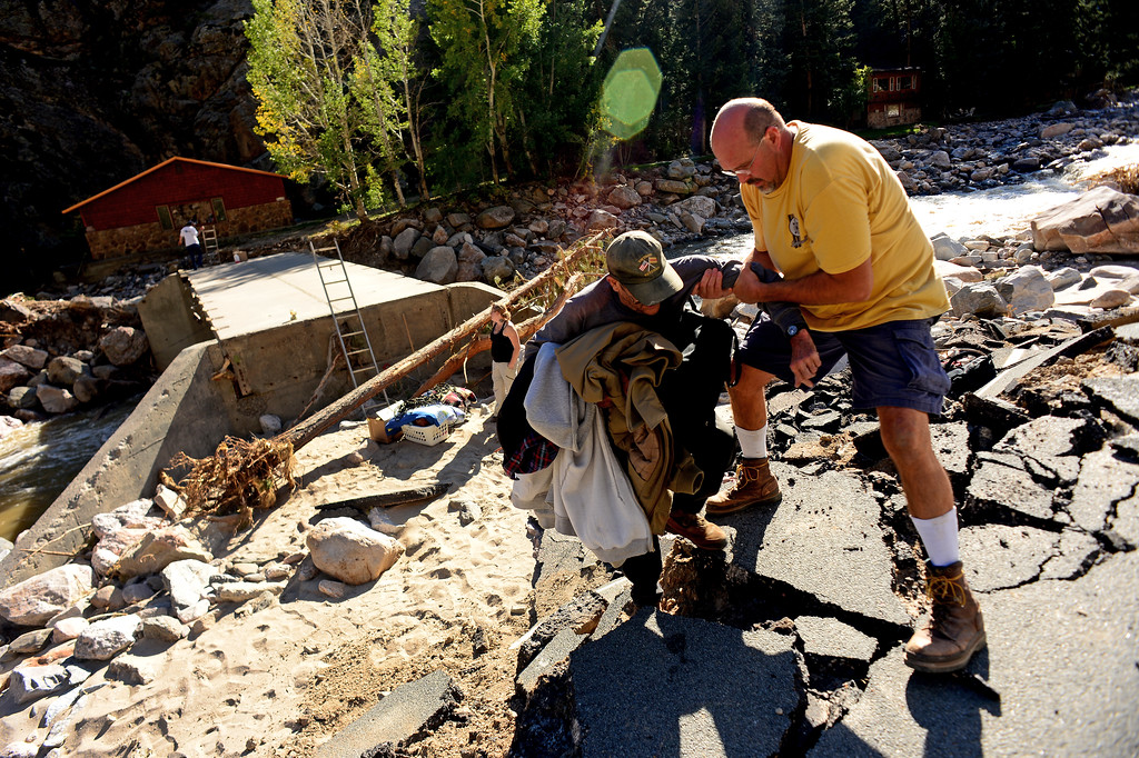 Description of . DRAKE, CO - OCTOBER 1:  Drake resident John Claus helps cabin caretaker Doug Smith, with some of his personal effects, up a steep incline onto Highway 34 in Drake, Co. October 1, 2013. Claus, Smith and their neighbors were allowed into their homes for the first time since the floods almost three weeks ago. Many of the homes are still standing but the surrounding property, the bridge and the highway are destroyed.  (Photo By Helen H. Richardson/ The Denver Post)