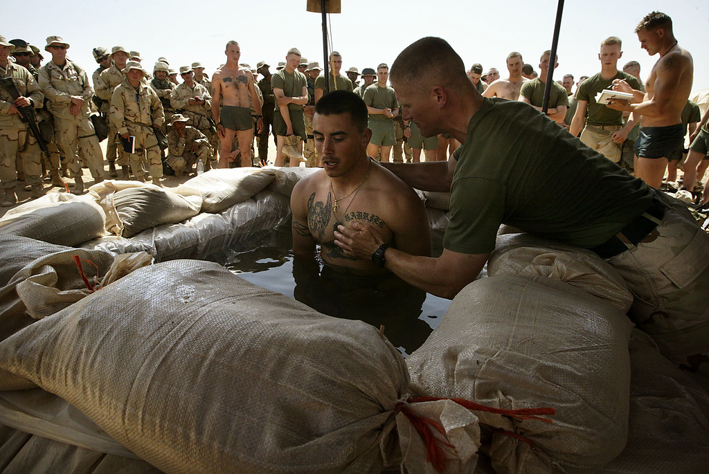 Description of . A Baptist chaplain baptizes U.S. marine Albert Martinez from Sunnyvalle, CA after a protestant Sunday service in a base in northern Kuwait close to the Iraqi border on March 16, 2003. A chaplain baptized infantrymen in the early morning sunlight, pushing their heads under the water of a field pool built from sandbags and plastic sheeting. REUTERS/Damir Sagolj