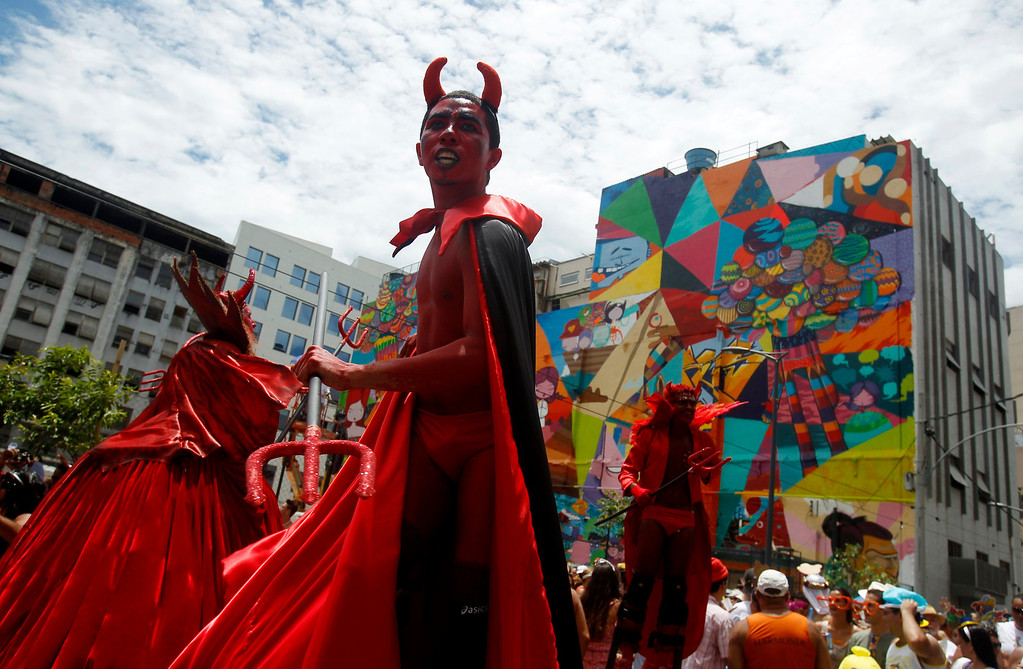 Description of . Revelers wearing devil costumes perform during an annual block party known as