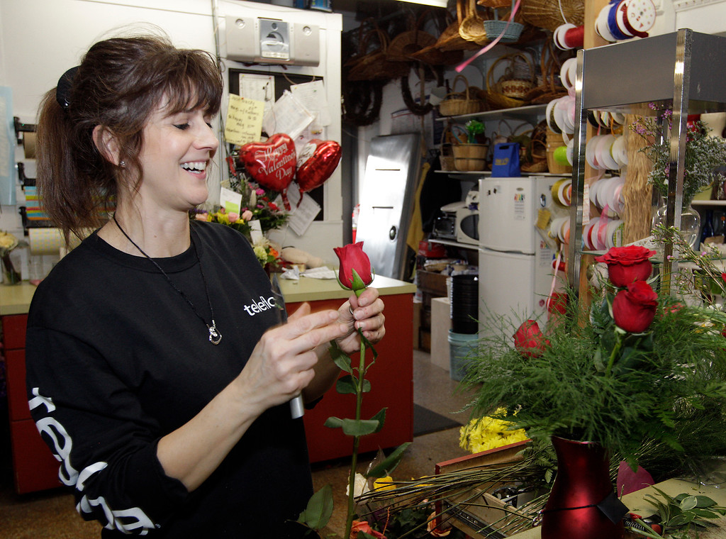 Description of . Oakwood Florist designer, Sheila Fuller puts the finishing touches on Telefloraís Heartstrings Bouquet for Amber Cardarella whose husband, Matt ordered her the bouquet for Valentineís Day thus winning the $15,000 diamond necklace in conjunction with Teleflora