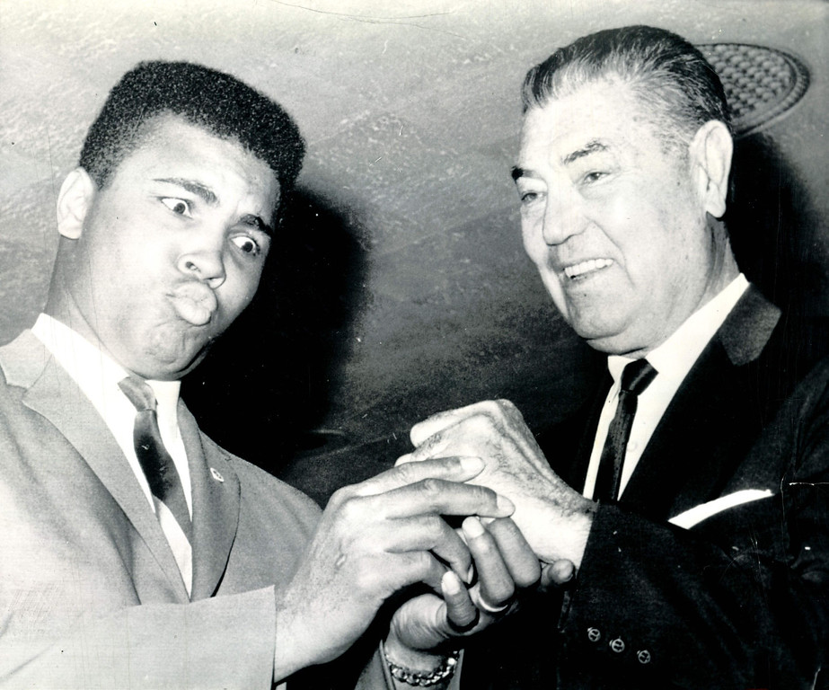 Description of . NEW YORK, JAN. 18--DEMPSEY'S FIST MAKES AN IMPRESSION ON CLAY--Heavyweight champion Cassius Clay may not only be acting when he looks with amazement at the fist of former heavyweight champion Jack Dempsey.  The two posed at Boxing Writers Association's annual dinner in New York last night.  Clay told the group that more white hopes would cure boxing ills and that with more white hopes like Dempsey and Gene Tunney around he could draw a $30 million gate fighting them. 1965. Credit: AP